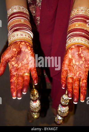 Henna hands Indian bride with traditional bangles - Stock Photo