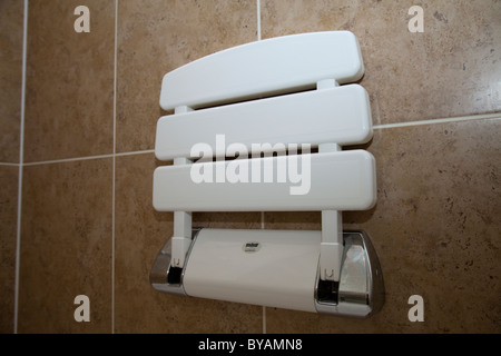 A disabled shower cubicle complete with chair and support handle bar in a residential property UK - Stock Photo