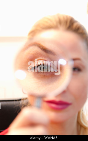 Woman looks thru magnifying glass - Stock Photo