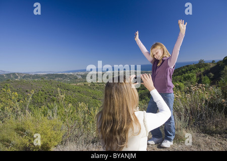 Mother photographing daughter with view - Stock Photo