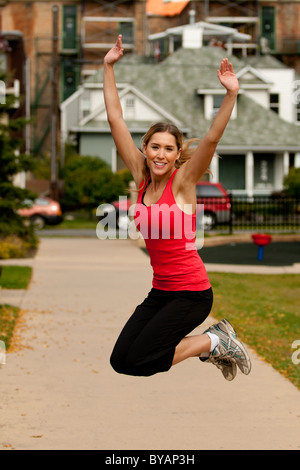 Outdoor spring training exercise in city park showing beautiful young blond Caucasian woman enjoying working out - Stock Photo