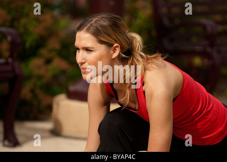 Outdoor spring training exercise in city park showing beautiful young blond Caucasian woman enjoying working out
