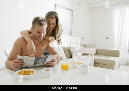 Young couple read paper at breakfast - Stock Photo