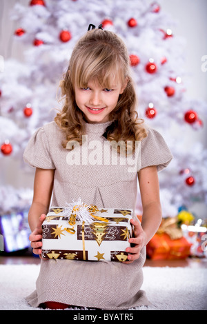Girl unpacking Christmas gifts - Stock Photo