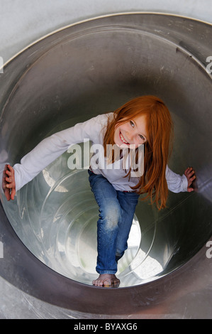 Girls playing in a tubular slippery dip at a playground - Stock Photo