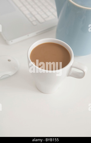 Cup of coffee beside a laptop at work - Stock Photo