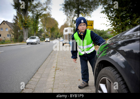 Little boy with reflective luminous vest is going to cross road - Stock Photo