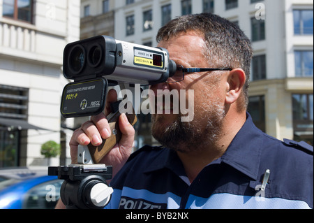 Police officer with a laser gun for speed monitoring, Berlin, Germany, Europe - Stock Photo