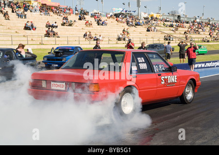 Australian Ford drag racing car performing a burnout prior to racing on the quarter mile. - Stock Photo