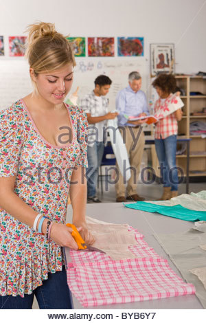 Serious student cutting fabric in home economics classroom - Stock Photo