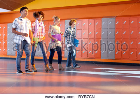 Students walking together near lockers in school hallway - Stock Photo