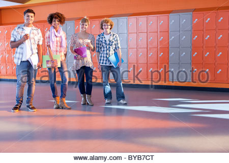 Students standing together near lockers in school hallway - Stock Photo