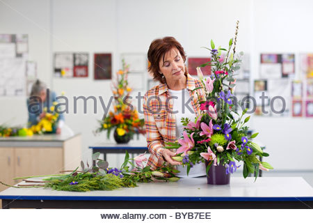 Serious woman putting flowers into floral arrangement in classroom - Stock Photo
