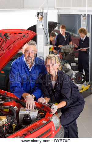 Teacher Helping Student With Car Engine Stock Photo