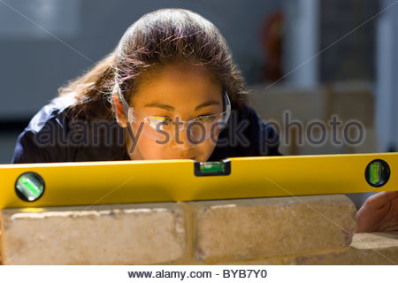 Bricklaying student using level on brick wall in vocational school - Stock Photo