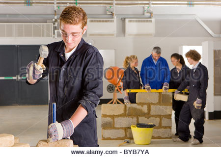 Student hammering chisel on brick in vocational school - Stock Photo