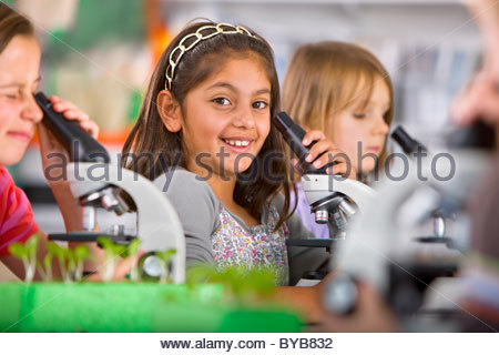 Smiling students peering into microscopes in science classroom - Stock Photo
