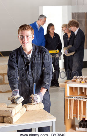Student with hammer and chisel in bricklaying vocational school - Stock Photo