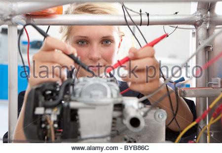 Student constructing electric vehicle prototype in vocational school - Stock Photo