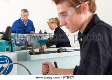 Teacher talking to students using lathe in vocational school - Stock Photo