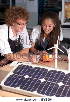 Students learning about wind power and solar panels in vocational school - Stock Photo