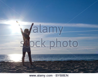 Excited woman with arms raised standing on beach - Stock Photo