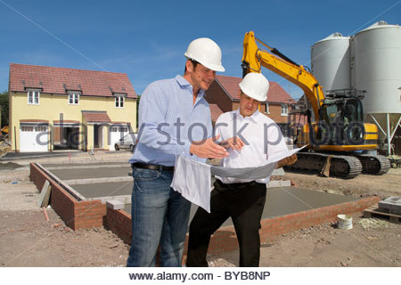 Construction workers holding blueprints talking on construction site - Stock Photo