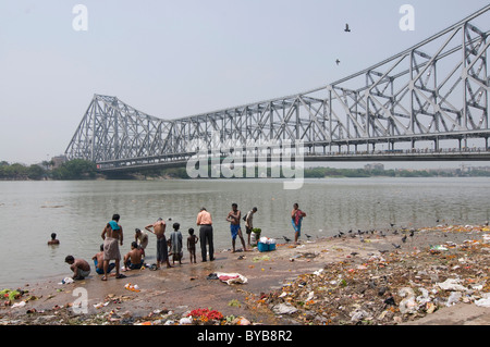 People washing themselves in the river in front of Howrah Bridge, Calcutta, Kolkata, India, Asia - Stock Photo