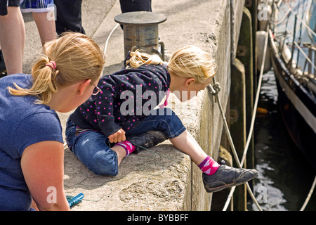 Blond girl crab fishing from quayside in Padstow Cornwall - Stock Photo