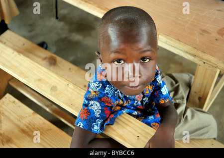 Young boy sitting on a school bench in a camp for victims of the January 2010 earthquake, Croix-des-Bouquets district, - Stock Photo