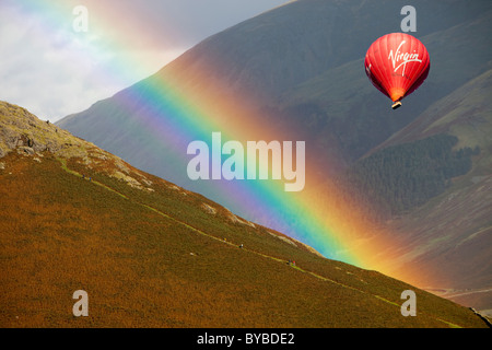 A rainbow arches over Steel Fell and walkers in the Lake District, UK, with a hot air balloon. - Stock Photo