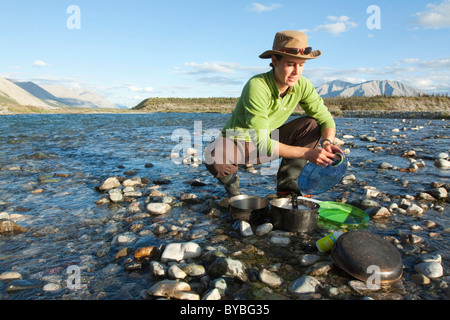 Young woman washing dishes in a river, camping, Mackenzie Mountains behind, Wind River, Yukon Territory, Canada - Stock Photo