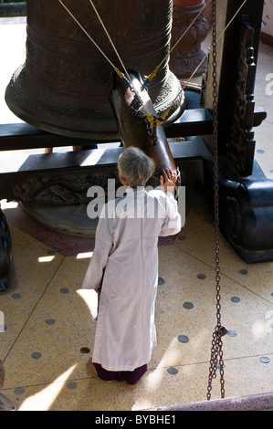 Old man with bell in Long Son Pagoda, Nha Trang, Vietnam, Asia - Stock Photo