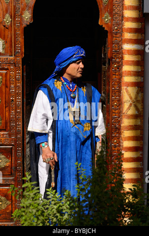 Profile of the traditional blue clothing costume of Berber Taureg man standing in ornate wood carved doorway in - Stock Photo