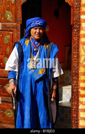 Man in traditional blue Berber garb standing in intricate inlaid wood carved doorway Marrakech Morocco - Stock Photo