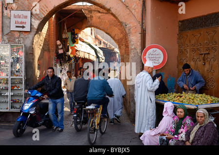 Traffic of pedestrians and bikes from the Djemaa el Fna square to shops in the narrow souk market medina of Marrakesh - Stock Photo