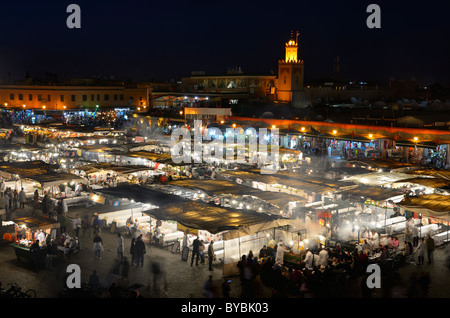 Crowds at the food vendors at night in Place Djemaa el Fna square souk in Marrakech Morocco - Stock Photo