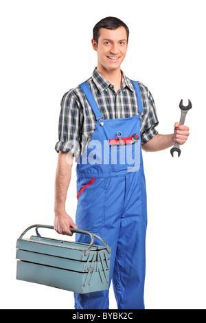 A repairman in blue overall holding a toolbox and wrench - Stock Photo