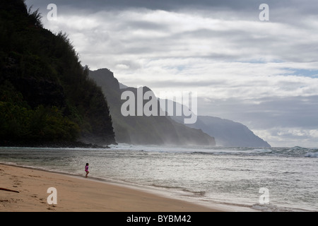 Kiki playing in the waves. The famous Na Pali Coast and a raging sea form the backdrop for a scene of a child playing - Stock Photo