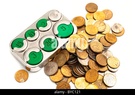 Moneybox coin holder (made in Soviet Union) and small change isolated on white background - Stock Photo