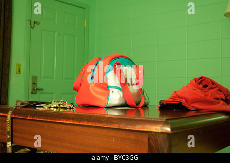 Keys, a shirt and a bag on a table in a cheap motel room painted green. - Stock Photo