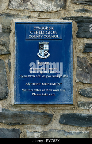 Bilingual sign fixed to Aberystwyth castle stating that visitors enter at their own risk, Wales. - Stock Photo