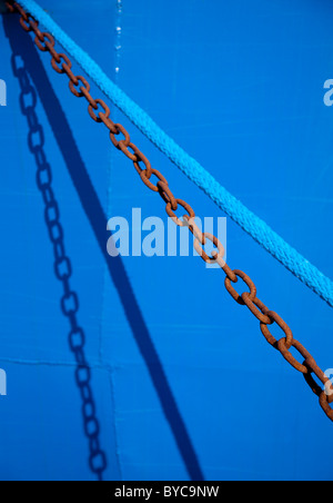 Metal chain and nylon blue rope side by side ( ship's mooring ropes )