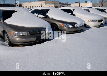 Snow-covered automobiles in Automobile Dealership parking lot Michigan USA - Stock Photo