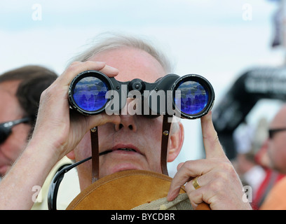 Spectator looking through binoculars at the sailing races during Cowes Week on the Isle of Wight, England, UK - Stock Photo