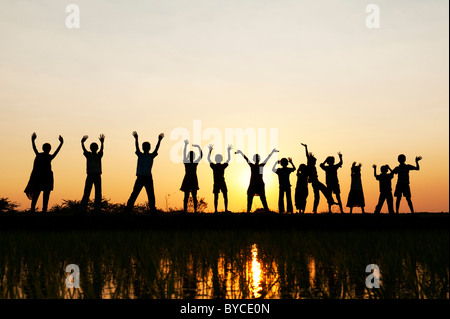 Silhouette Indian girls and boys jumping and waving standing on a rice paddy field at sunset. Andhra Pradesh, India - Stock Photo