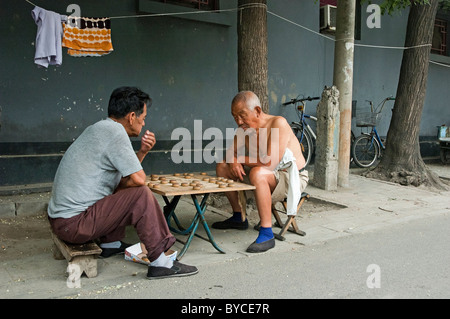 Old men playing Xiangqi or Chinese Chess in Hutong District of Beijing, China - Stock Photo