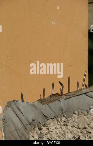 sharp metal steel nails used as a burglar intruder deterrent on high wall - Stock Photo