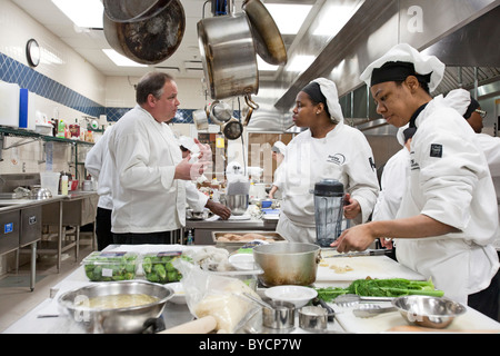 Instructor John Adamski works with students preparing food at the Dorsey Culinary Academy, a private career training - Stock Photo