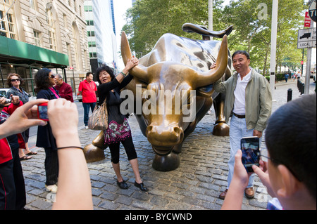 Tourists posing for photos besides the charging bull sculpture close to Wall Street , New York City, America, USA - Stock Photo